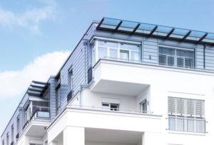 Budynek z dużymi balkonami. Budynek posiada okna i okna balkonowe. Okna mają rolety zewnętrzne.