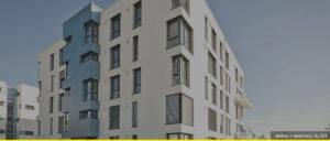 Budynek czteropiętrowy z dziesiątkami okien w różnych rozmiarach. Budynek posiada również balkony.