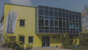 Na zdjęciu pokazany jest budynek firmy Aldo. Budynek jest w dużej części przeszklony.