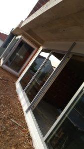 Ściana budynku ze świeżo wstawionymi oknami i przesuwanymi drzwiami balkonowymi.