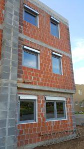 Budynek w surowym stanie. Budynek ma świeżo wstawione okna z roletami zewnętrznymi