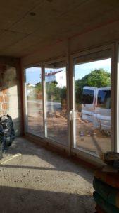 Zdjęcie z wewnątrz budynku przedstawiające świeżo wstawione okna i przesuwane drzwi balkonowe