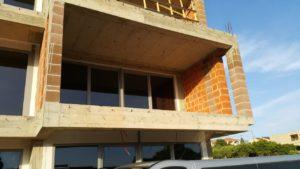 Przeszklona ściana budynku z przesuwanymi drzwiami balkonowymi.