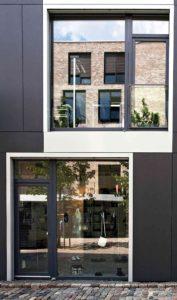 Ściana budynku z dużymi oknami i parą drzwi balkonowych.