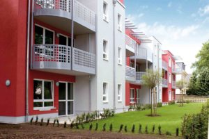 Szereg podobnych budynków z okami o różnych rozmiarach. Budynki mają balkony i drzwi balkonowe.