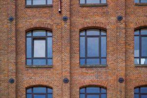 Ściana budynku o kolorze cegły. W ścianie są duże zaokrąglone okna.