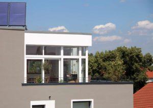 Zbliżenie na fragment budynku z przeszkloną ścianą budynku.Na dachu budynku są panele słoneczne.