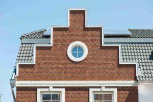 Kawałek budynku, na dachu są panele słoneczne. Na środku jest okrągłe okno, poniżej są okna o kształcie prostokątów.