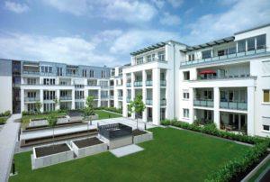 Osiedle z budynkami trzypiętrowymi z dużą ilością okien w różnych rozmiarach. Budynki posiadają balkony.