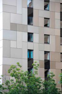 Ściana budynku z dużą liczbą małych okien ułożonych na tym samym poziomie.
