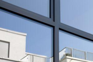 Zbliżenie na czarną ramkę okna.W oknie odbija się fragment budynku