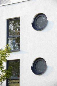 W ścianie budynku są dwa okna w kształcie okręgów i dwa w kształcie prostokątów.