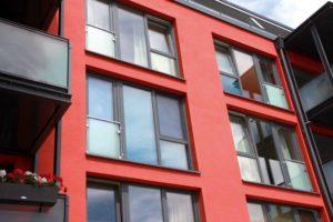 Budynek o kolorze czerwonym. W ścianie budynku znajdują się okna o różnych rozmiarach.