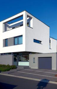 Biały budynek z oknami o różnych rozmiarach. W prawym dolnym rogu znajduje się garaż