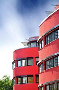 Czerwony zaokrąglony budynek z dużą liczbą okien. Okna są ułożone w rzędach obok siebie.