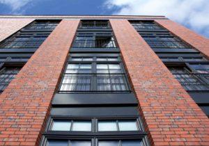 Ściana budynku w kolorze cegły z dużymi prostokątnymi oknami. Nad dużymi oknami są okna mniejsze.