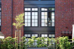 Fragment ściany budynku w kolorze cegły. W ścianie budynku są duże okna.