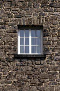 Ściana budynku z jednym oknem pośrodku.Okno ma białą ramkę.