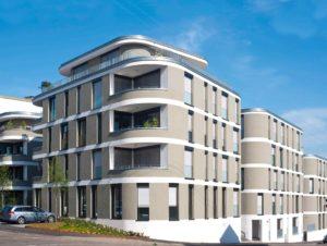 Budynek z dużą liczbą różnej wielkości okien. Na brzegu budynku są balkony