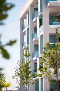 Budynek wielopiętrowy z dużą liczbą balkonów. Budynek ma nowoczesny design.
