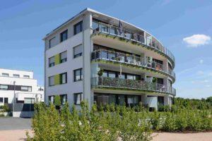 Budynek trzypiętrowy z dużymi balkonami. W ścianie budynku są prostokątne okna z roletami zewnętrznymi.