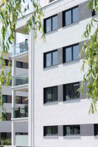 Ścian budynku kilkupiętrowego. Budynek posiada okna w różnych rozmiarach.