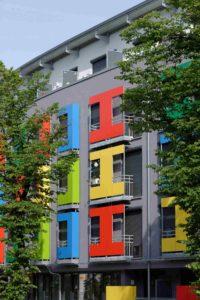 Budynek z kolorowymi elementami. Okna mają rolety zewnętrzne.