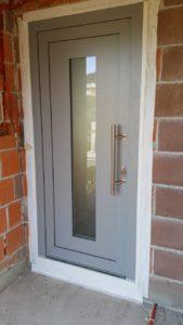 Szare drzwi z szklanym paskiem biegnącym od góry do dołu.