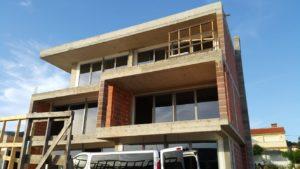 Budynek ze świeżo wstawionymi oknami. Okna są na prawi całej ścianie budynku.
