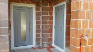 Po lewej stronie są szare drzwi z przeszklonym paskiem, a po prawej stronie są szare drzwi z klamką.