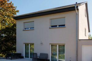 Ściana budynku z drzwiami balkonowymi i oknami.Okna są zasłonięte roletami zewnętrznymi