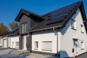 Budynek z panelami słonecznymi na dachu. W ścianach budynku są małe , duże okna i drzwi.