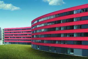Duży budynek z setkami okien ułożonymi w rzędach jeden pod drugim.Okna przedzielane były czerwone pasy.