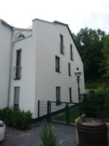 Budynek z małymi oknami i większymi drzwiami balkonowymi. Okna mają rolety zewnętrzne.
