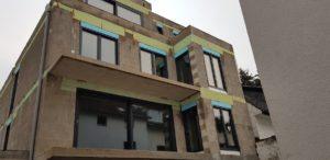 Budynek ze świeżo wstawionymi oknami w różnych rozmiarach. Okna są w kształcie prostokątów.n