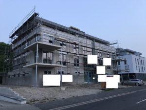 Budynek ze świeżo wstawionymi okami i drzwiami przesuwanymi. Okna są w różnych rozmiarach.