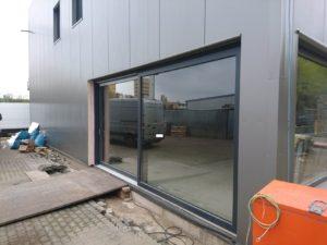 Budynek z przesuwanymi drzwiami. Na środku ściany budynku są dwa małe prostokątne okna.