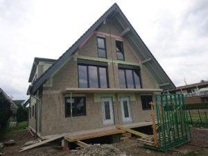 Budynek ze spadzistym dachem. Budynek ma świeżo wstawione drzwi i okna.